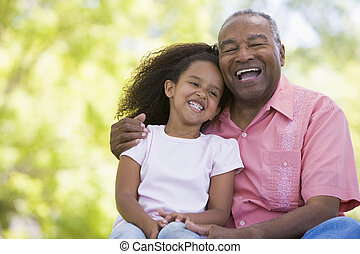 Grandfather and granddaughter outdoors smiling