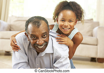 Grandfather And Granddaughter Playing Together At Home