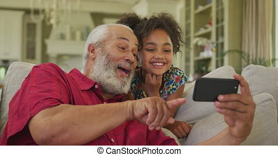 Grandfather and granddaughter using smartphone at home - ...