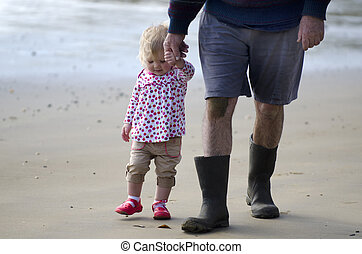 Grandfather and granddaughter walks on the beach