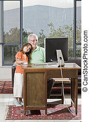 grandfather and granddaughter with computer
