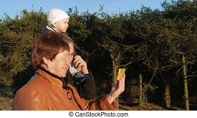 Grandfather and grandmother with her grandson walk in the park and talk on the mobile phone with their relatives at sunset. Video communication over the Internet