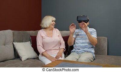 Enthusiastic grandfather and grandmother with VR headset helmet play games, watch virtual reality 3D 360 video. Family of senior man and woman at home. Future technology. VR goggles, glasses