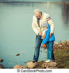 Grandfather and grandson are crossing the river on the stones