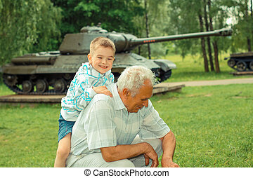 Grandfather and grandson are photographed on a background of vintage tank