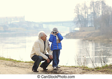 Grandfather and grandson are photographed on a vintage camera