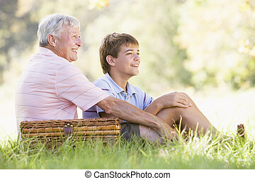 Grandfather and grandson at a picnic smiling