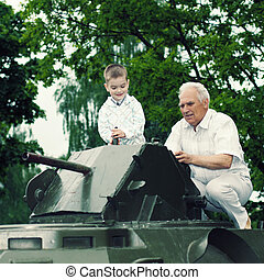 Grandfather and grandson climbed on old vintage military tank and explore its