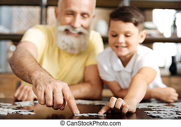 Grandfather and grandson connecting two pieces of jigsaw puzzle