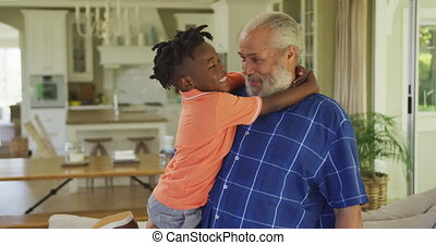 Senior African American man and his grandson spending time at home together, standing in the living room, embracing and smiling, in slow motion.