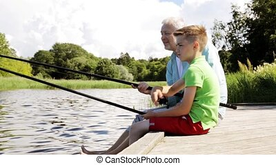 grandfather and grandson fishing on river berth - family, ...