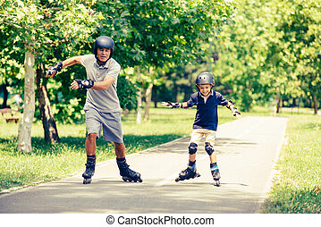 Grandfather and grandson having fun roller skating in the park