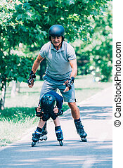 Grandfather and grandson having fun, roller skating in the park