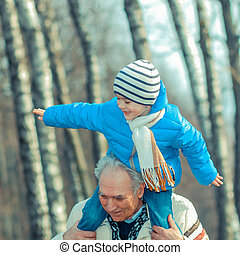 Grandfather and grandson indulge. Grandfather Carrying Grandson On His Shoulders. The grandfather makes movies on old movie camera.