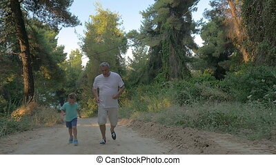Grandfather and grandson jogging in the forest - Slow motion...