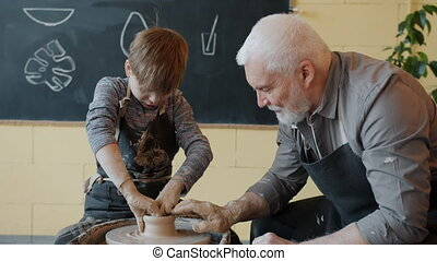Grandfather and grandson are manufacturing ceramic pot from clay on pottery wheel talking concentrated on creative activity. People and hobby concept.