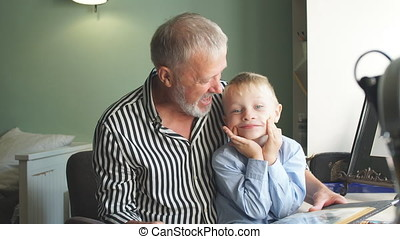 Grandfather and grandson on sofa at home. Grandpa and...