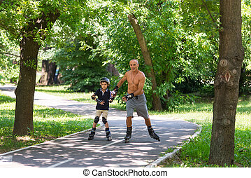 Grandfather and grandson roller skating outdoors