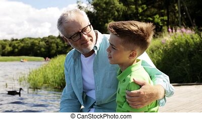 grandfather and grandson sitting on river berth 23 - family,...