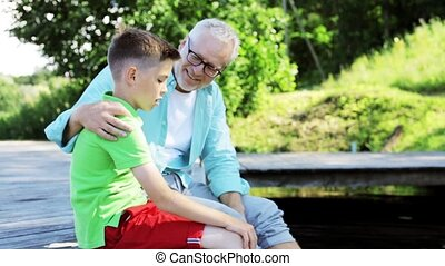 grandfather and grandson sitting on river berth 27 - family,...
