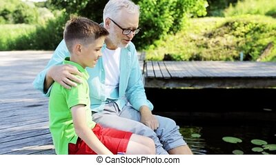 grandfather and grandson sitting on river berth 29 - family,...