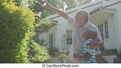 Grandfather and grandson spending time together - Side view ...