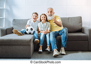 Grandfather and his grandchildren watching football match together
