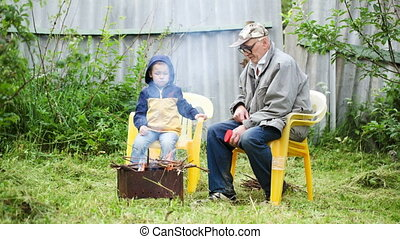 Grandfather and his grandson sitting by the fire outdoor