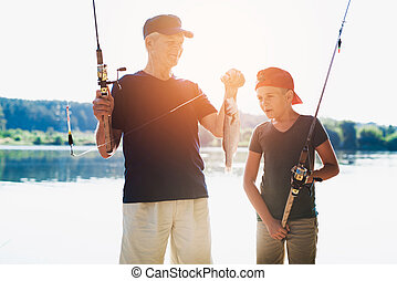 Grandfather and his grandson stand on the river bank with spinning rods and look at the fish that the old man caught