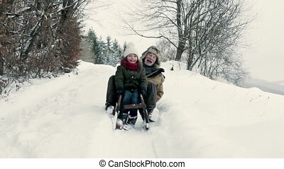 Grandfather and small girl sledging on a winter day. - ...