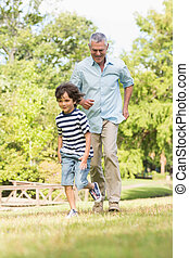 Grandfather and son running on grass in park