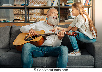 Grandfather chatting with granddaughter while holding guitar...