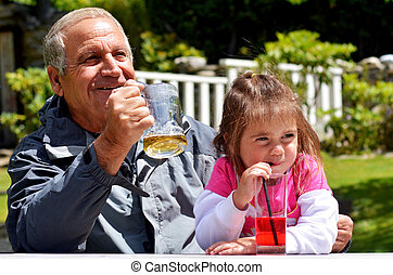 Grandfather drinks with his grandchild