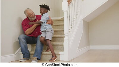 Grandfather embracing his grandson at home - Senior African ...