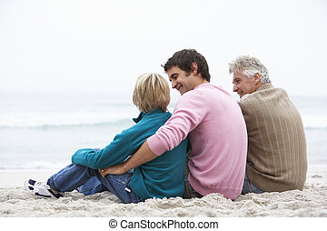Grandfather, Father And Grandson Sitting On Winter Beach