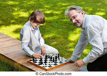 Grandfather, father and kids playing chess.