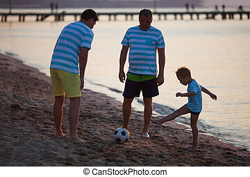 Grandfather, Father and Son Kicking Ball on Beach
