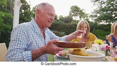 Grandfather feeding his grandson while having lunch outdoors...