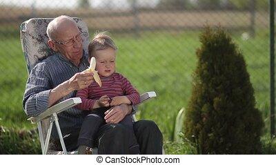 Grandfather giving banana to his grandson outdoor.