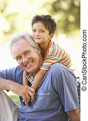 Grandfather Giving Grandson Ride On Back In Park