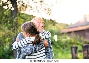 Grandfather giving his grandaughter a hug. Senior man and a...