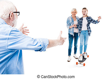 grandfather, grandmother and happy granddaughter with skateboard isolated on white