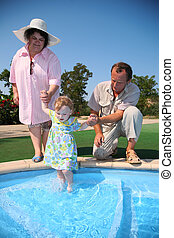 Grandfather, grandmother hold granddaughter in pool