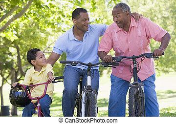 Grandfather grandson and son bike riding