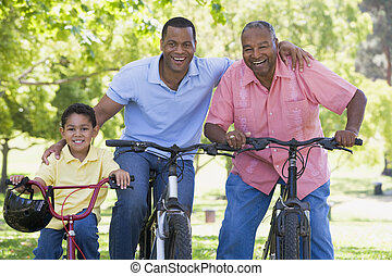 Grandfather grandson and son bike riding.