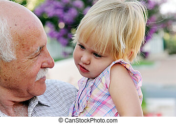 grandfather holding his 2 year old granddaughter