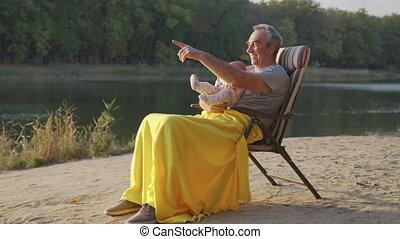 Grandfather Holding Newborn Baby Granddaughter Outdoors. - ...