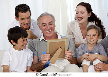 Grandfather looking at a photo with his family