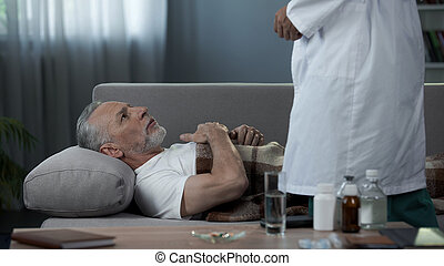 Grandfather lying on couch and complaining doctor of heart pain, healthcare