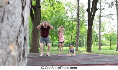 Grandfather playing and jumping with grandchildren outside...